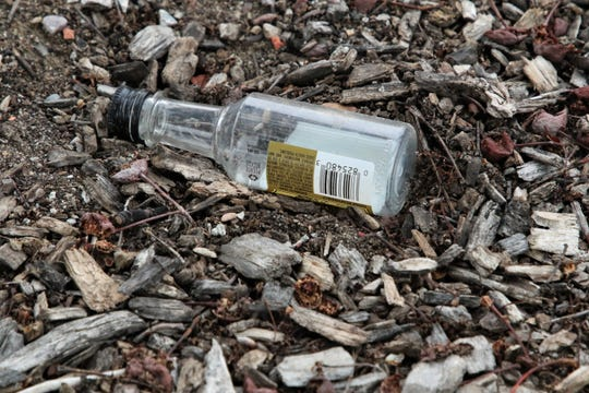 An empty miniature liquor bottle is seen on the ground in a parking lot in downtown Farmington, New Mexico.