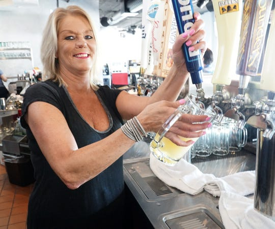 Maraschinos Pub bartender Stacey McDonald pours a beer from a tap at the Cherry Hill Village bar.