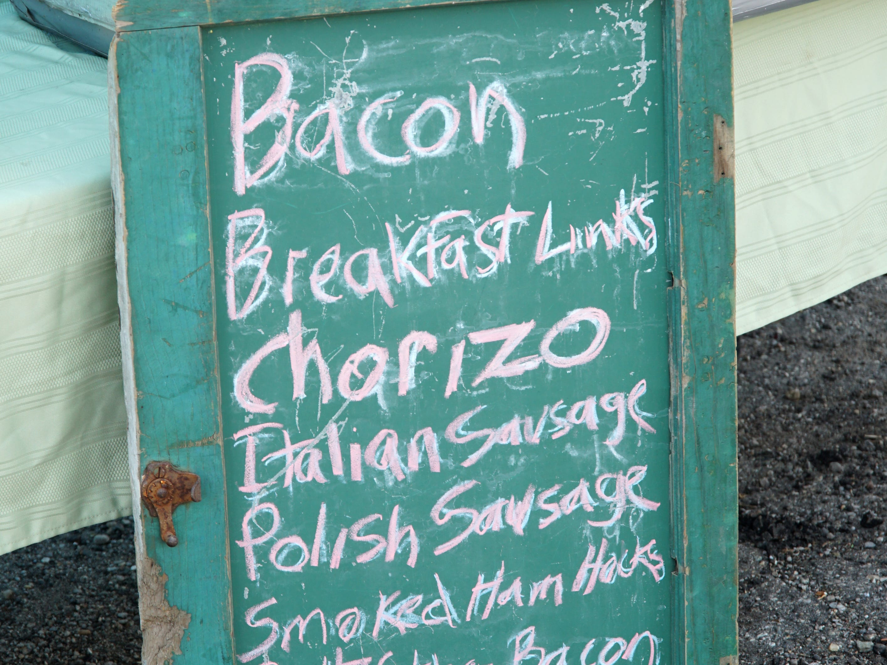 A sandwich board at the May 16 market noting the kinds of pork products a vendor's selling.