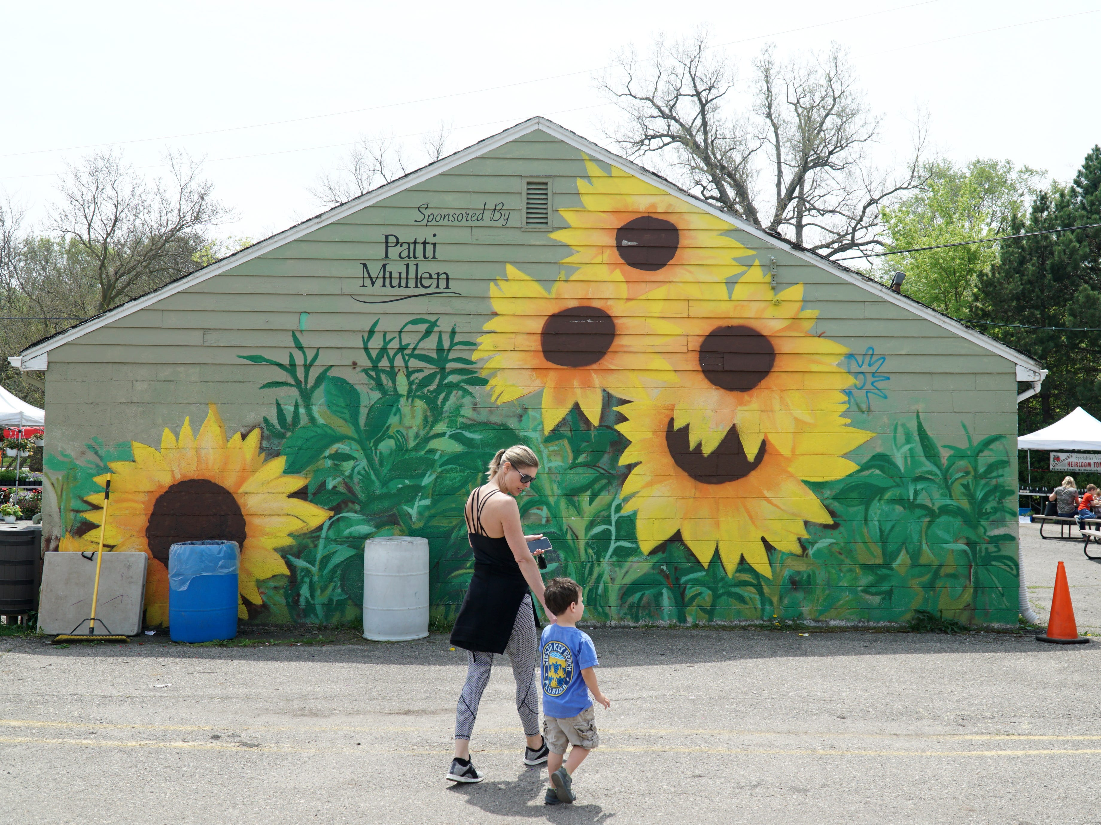 Lauren Poole-Romeo walks with friend of her family Matthew Corriveau near a sunflower mural at the Northville Famers Market on May 16. The duo were going to do some shopping after they had lunch at one of the market's food stalls.