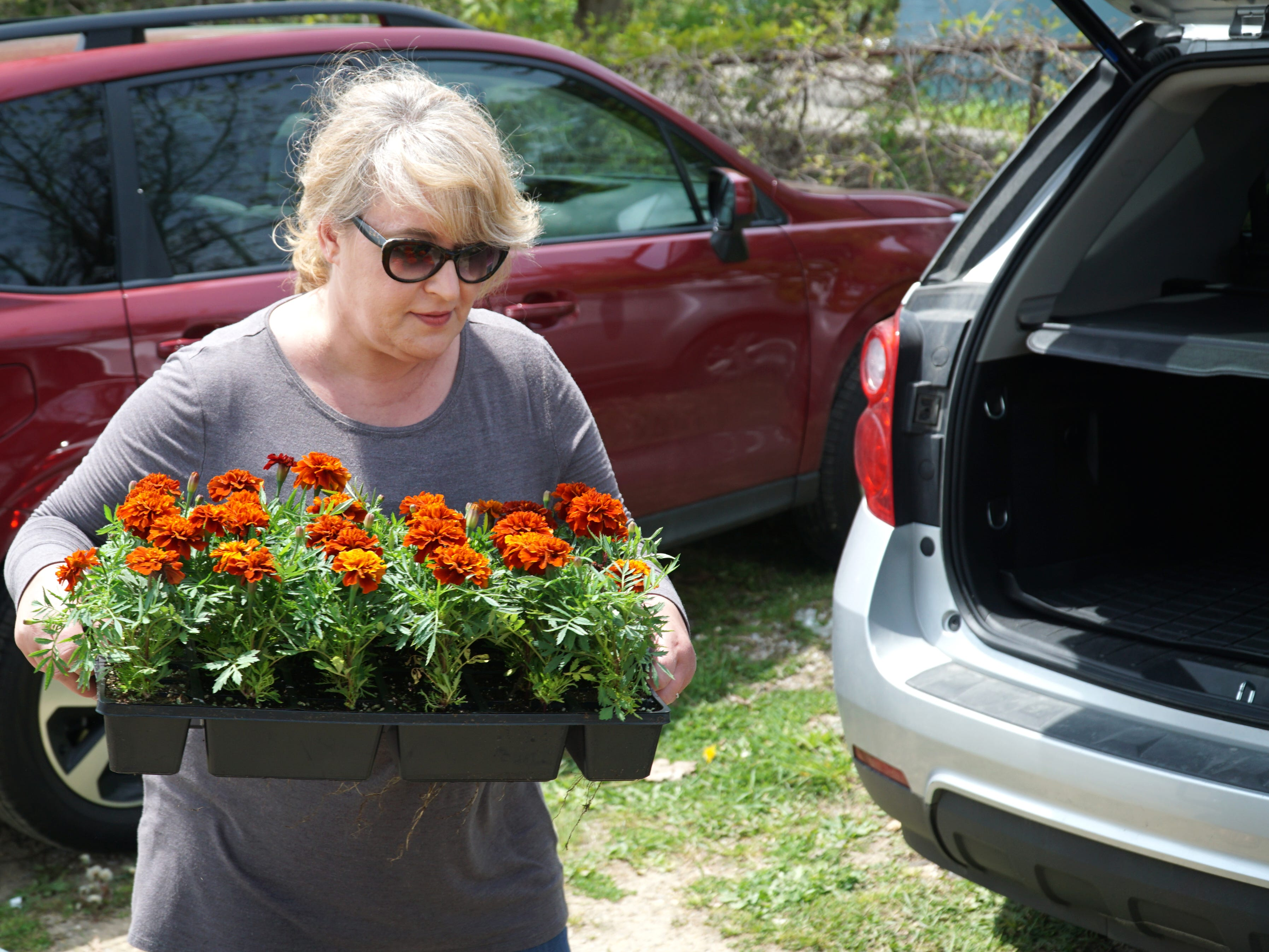 Sandra Ralston prepares to load up her Northville Farmers Market purchases on May 16.