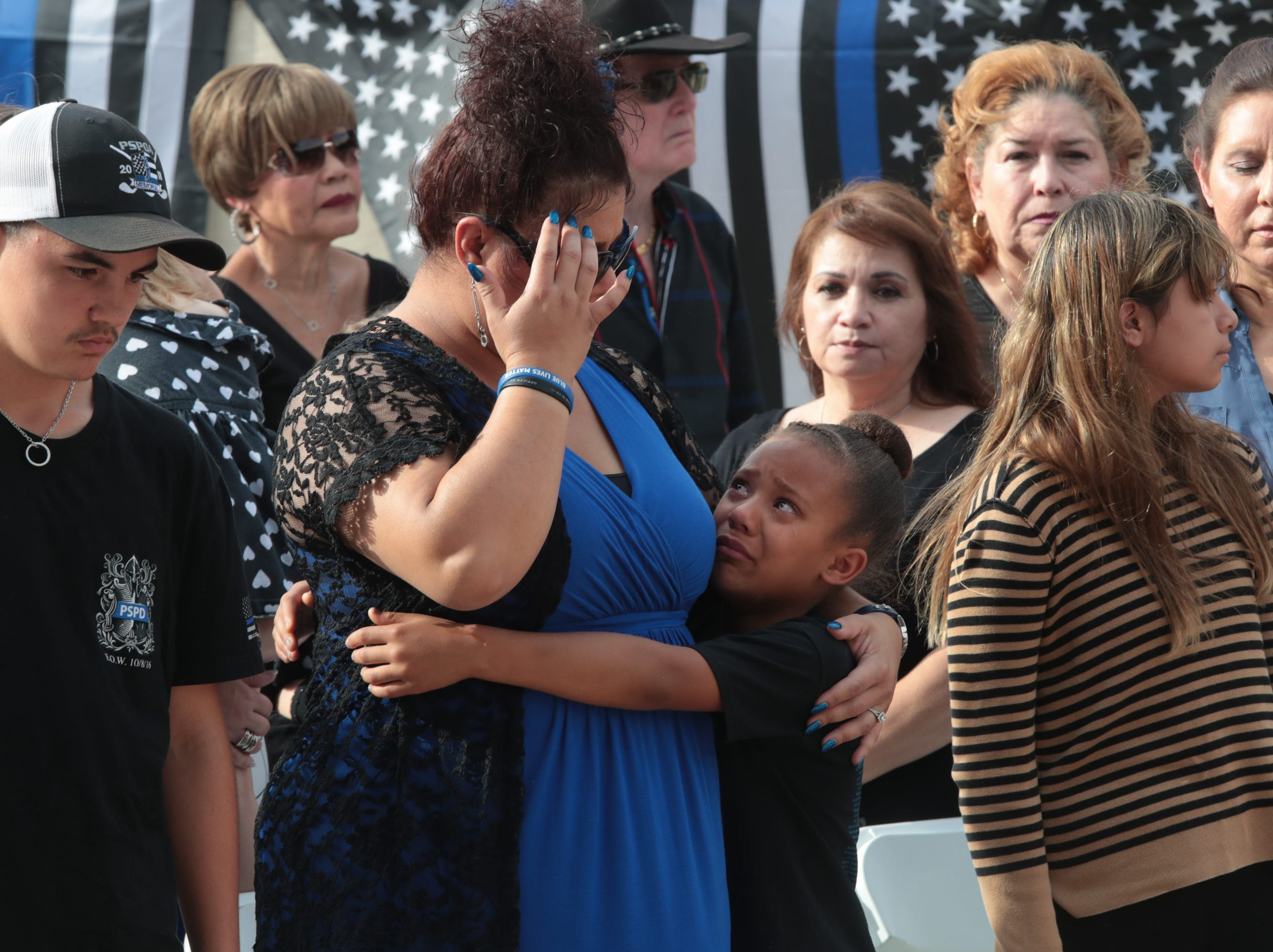 Sophia Murray embraces her mother Andrea Murray, the stepdaughter of Officer Vega, during a ceremony honoring fallen Palm Springs police officers on Peace Officers Memorial Day, Palm Springs, Calif., May 15, 2019.