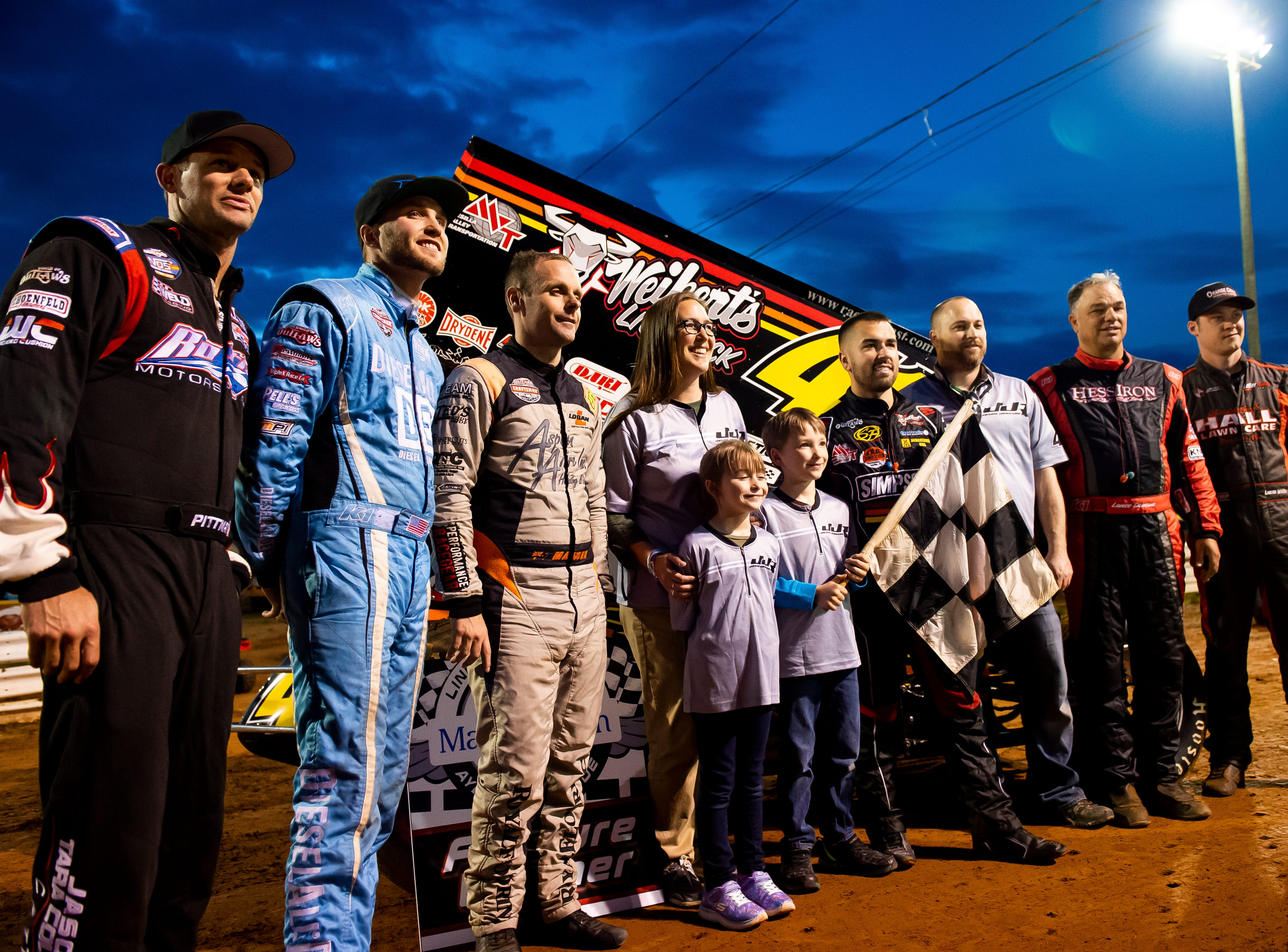 Ayden Gora, 8, of Duncannon, holds the checkered flag as he poses for photos with his family and a host of drivers before the start of the World of Outlaws Gettysburg Clash at Lincoln Speedway in Abbottstown on Wednesday, May 15, 2019. Ayden was able to serve as an honorary crew member with David Gravel's team thanks to the Make-A-Wish Foundation,