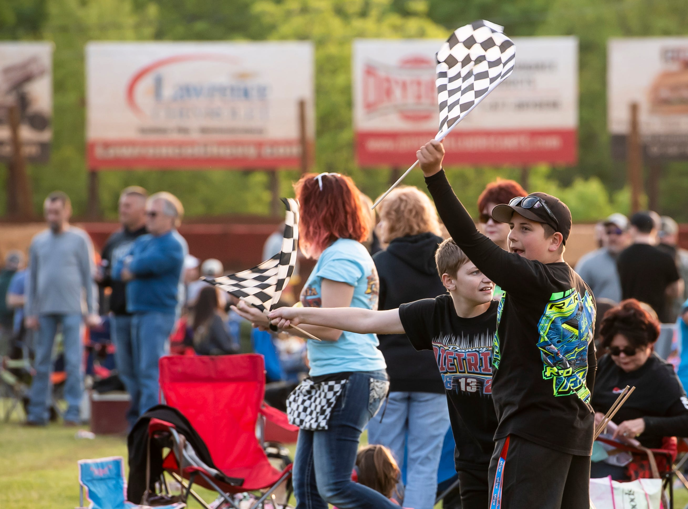 Cameron Klinedinst, 13, (left) and Aizik Shoap, 14, wave flags as drivers participate in the time trials during the World of Outlaws Gettysburg Clash at Lincoln Speedway in Abbottstown on Wednesday, May 15, 2019.