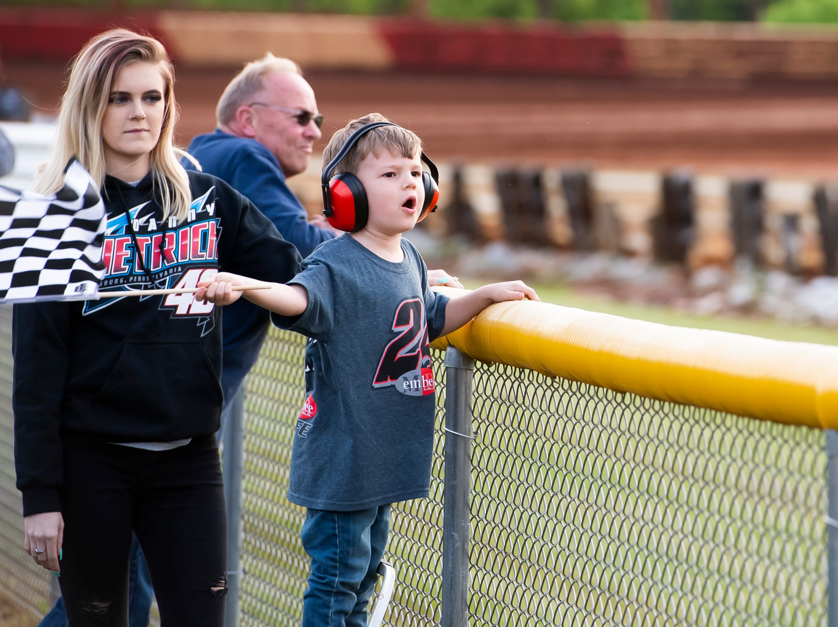 Landon Nickol, 3, of Dover, waves a checkered flag as his mother, Taylor Fowler, looks on as drivers race in the time trials during the World of Outlaws Gettysburg Clash at Lincoln Speedway in Abbottstown on Wednesday, May 15, 2019.