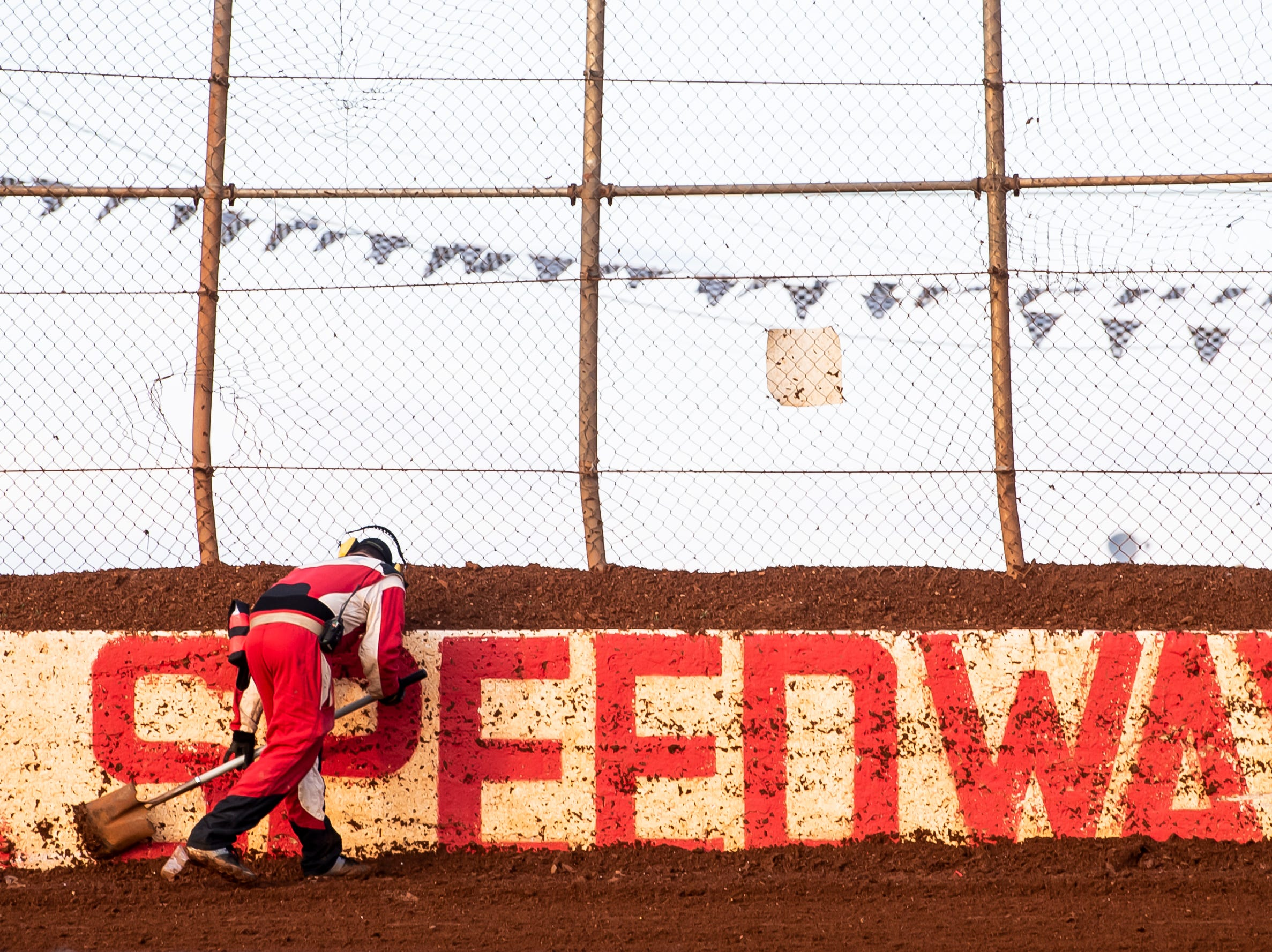A track crew member scrapes mud off the wall during the World of Outlaws Gettysburg Clash at Lincoln Speedway in Abbottstown on Wednesday, May 15, 2019.