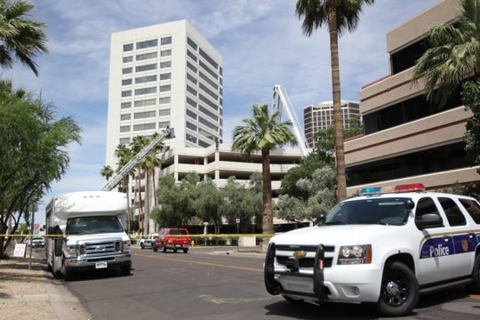 """Phoenix police and fire officials are negotiating with an """"adult male in crisis"""" who is standing on a six-story parking garage."""