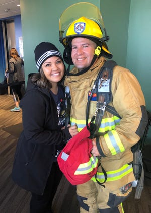 Gilbert Aguirre, right, with his wife, Tiffanie, left, in March at the Leukemia and Lymphoma Society Firefighter Stair Climb in Seattle.