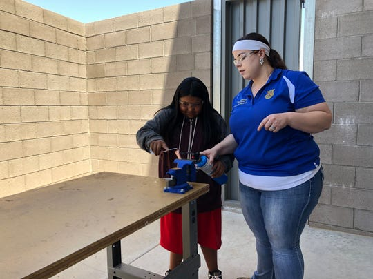 Canyon View High School agriculture teacher Kerilyn Brothers shows a Havasupai Elementary School student how to solder a piece of copper for a class project.