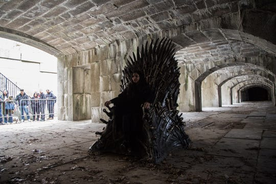 A 'Game of Thrones' fan poses for a photo next to the Iron Throne, which has been set up in Fort Totten Park in Queens, New York, USA.