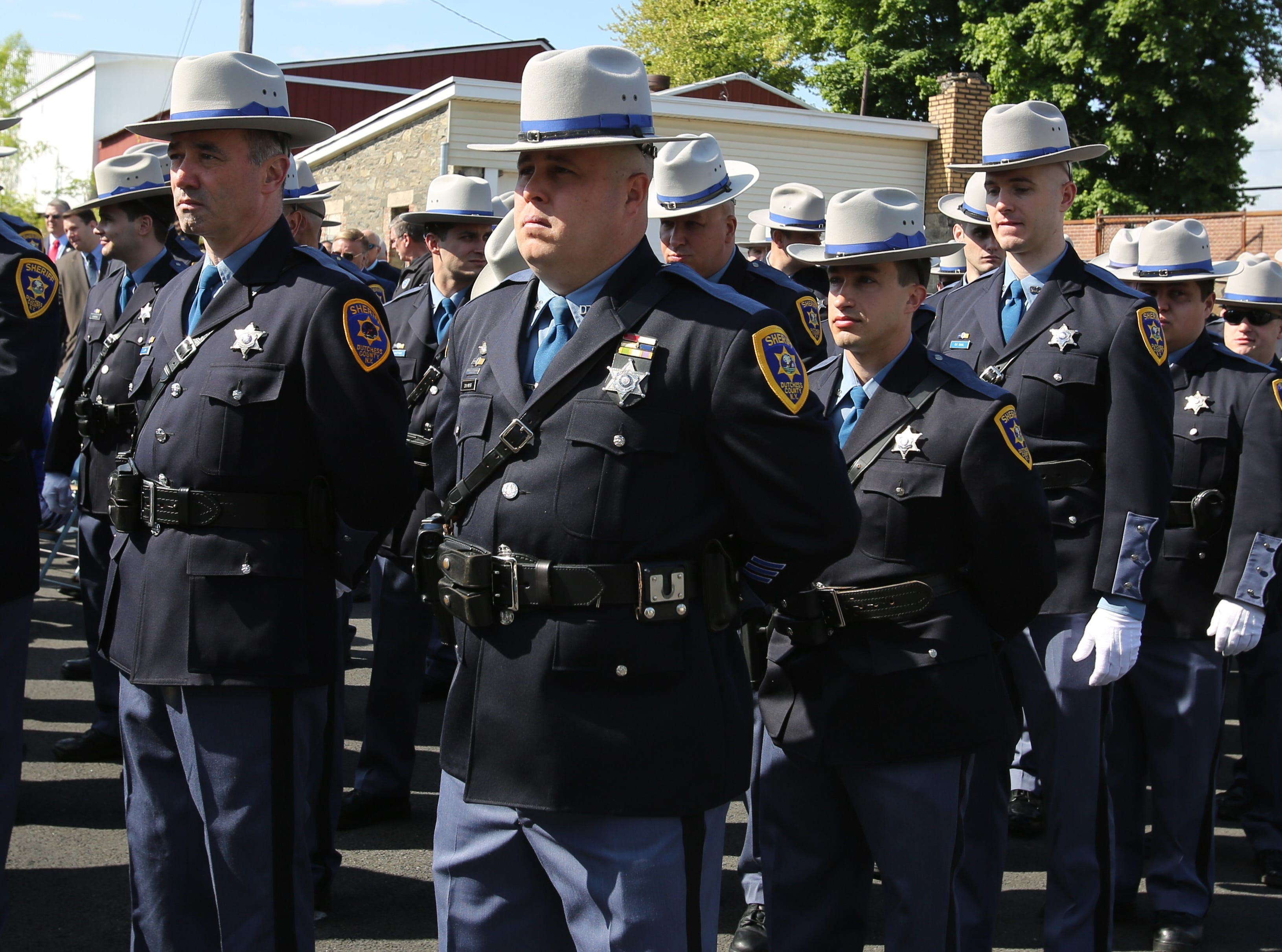 Multiple law enforcement officials stand in the parking lot of the Dutchess County Sheriff's Office in honor of Memorial Day on May 16, 2019.