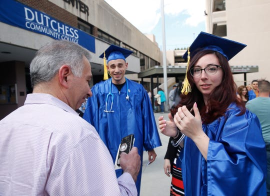 Dutchess Community College nursing students, from left, Noah Norstein and Laura Sarnicola prepare to have Joseph Sarnicoal take their photo before entering the commencement ceremony on May 16, 2018