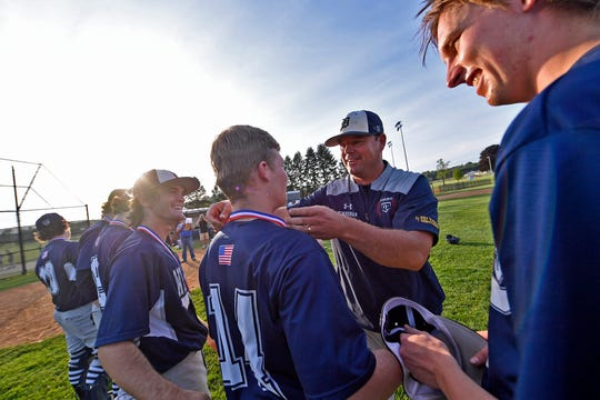 Dallastown head coach Greg Kinneman places a first place medal on Darren Sciortino after the Wildcats defeated Gettysburg 8-0 to win the YAIAA baseball championship, Thursday, May 16, 2019.