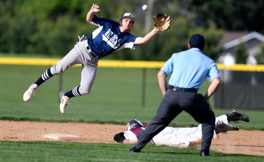 Dallastown second baseman Cam Urey makes a leaping catch on a throw from catcher Julian Bailey as Simeon Davis of Gettysburg slides in safely during the YAIAA baseball championship, Thursday, May 16, 2019.