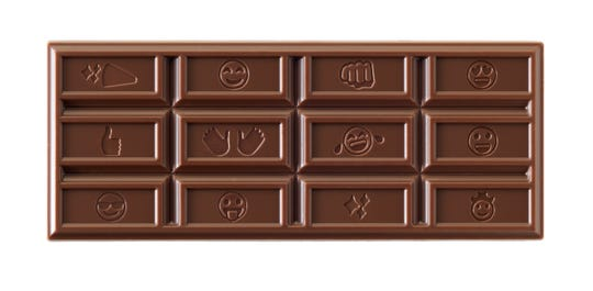 An unwrapped Hershey bar shows the new design stamped with different emojis.
