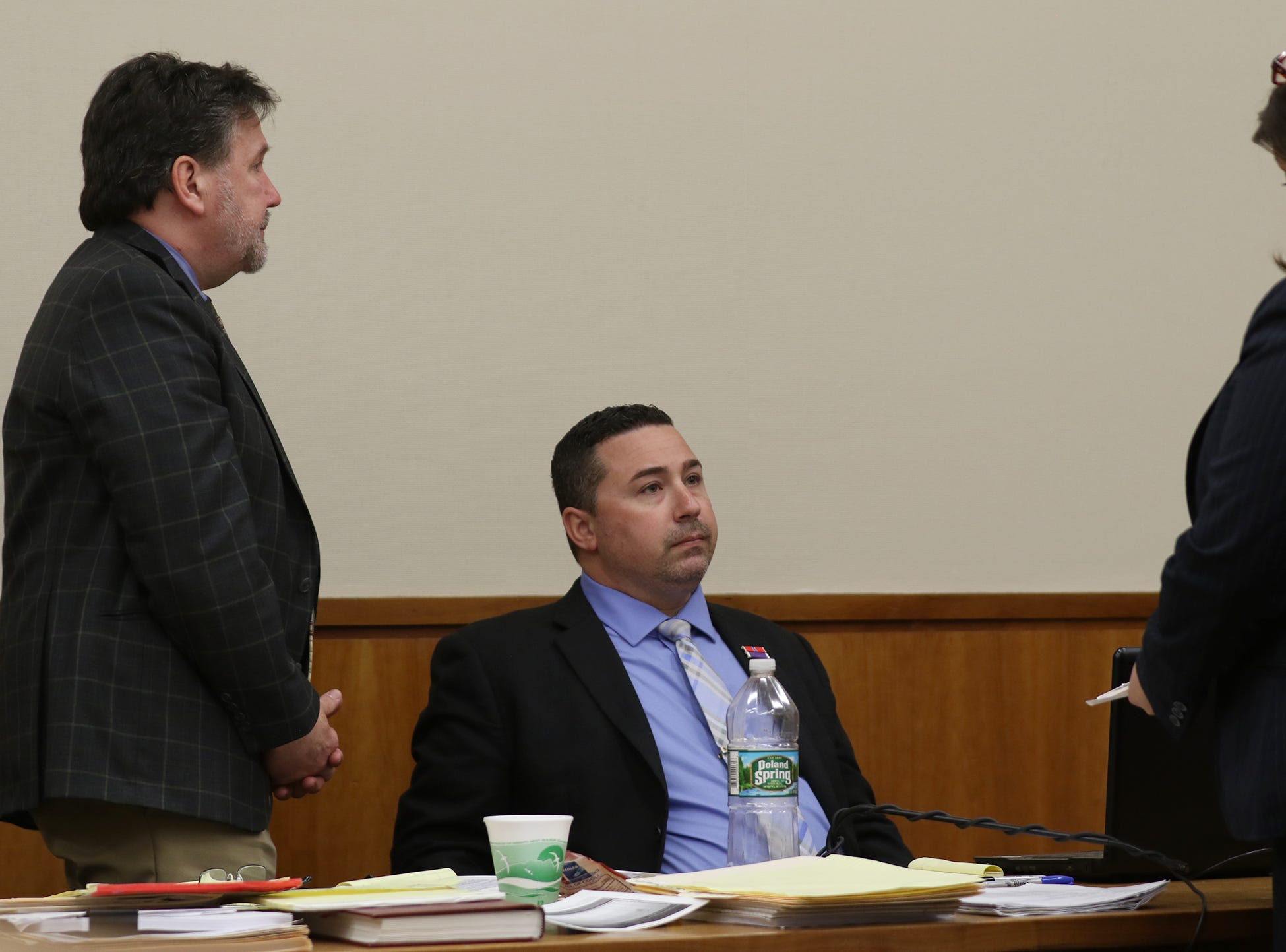 Rochester Police Officer Michael Sippel looks on as Monroe County District Attorney Gina Clark shows his defense attorney, Clark Zimmerman, a photo of a man that Christopher Pate was mistaken for.  Zimmermann had just objected to the use of the photo that Clark tried to introduce.