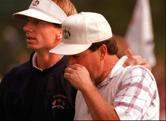 Brad Faxon ,left, comforts teammate Jay Haas, right, after Haas lost his match with Phillip Walton giving Europe a victory in the 1995 Ryder Cup at Oak Hill Country Club.