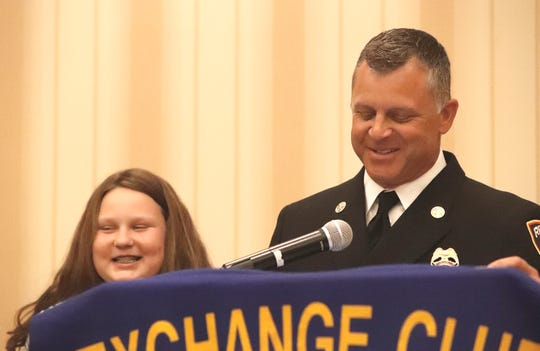 Redding Fire Chief Cullen Kreider, right, stands beside Aubrey Stoke to accept a Firefighter of the Year award on behalf of Aubrey's father, Jeremy Stoke, who died in last summer's Carr Fire. The posthumous award was presented May 16, 2019, by The Exchange Club of Redding at the Red Lion Hotel.