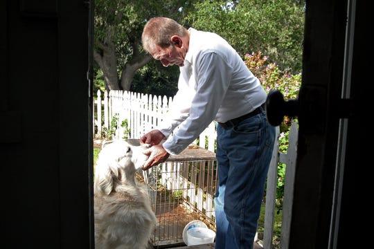 Rick Davis carefully balances a dog bone on his golden retriever, Cooper's, face. Davis registered Cooper to vote in protest of online voter registration. May 16, 2019.