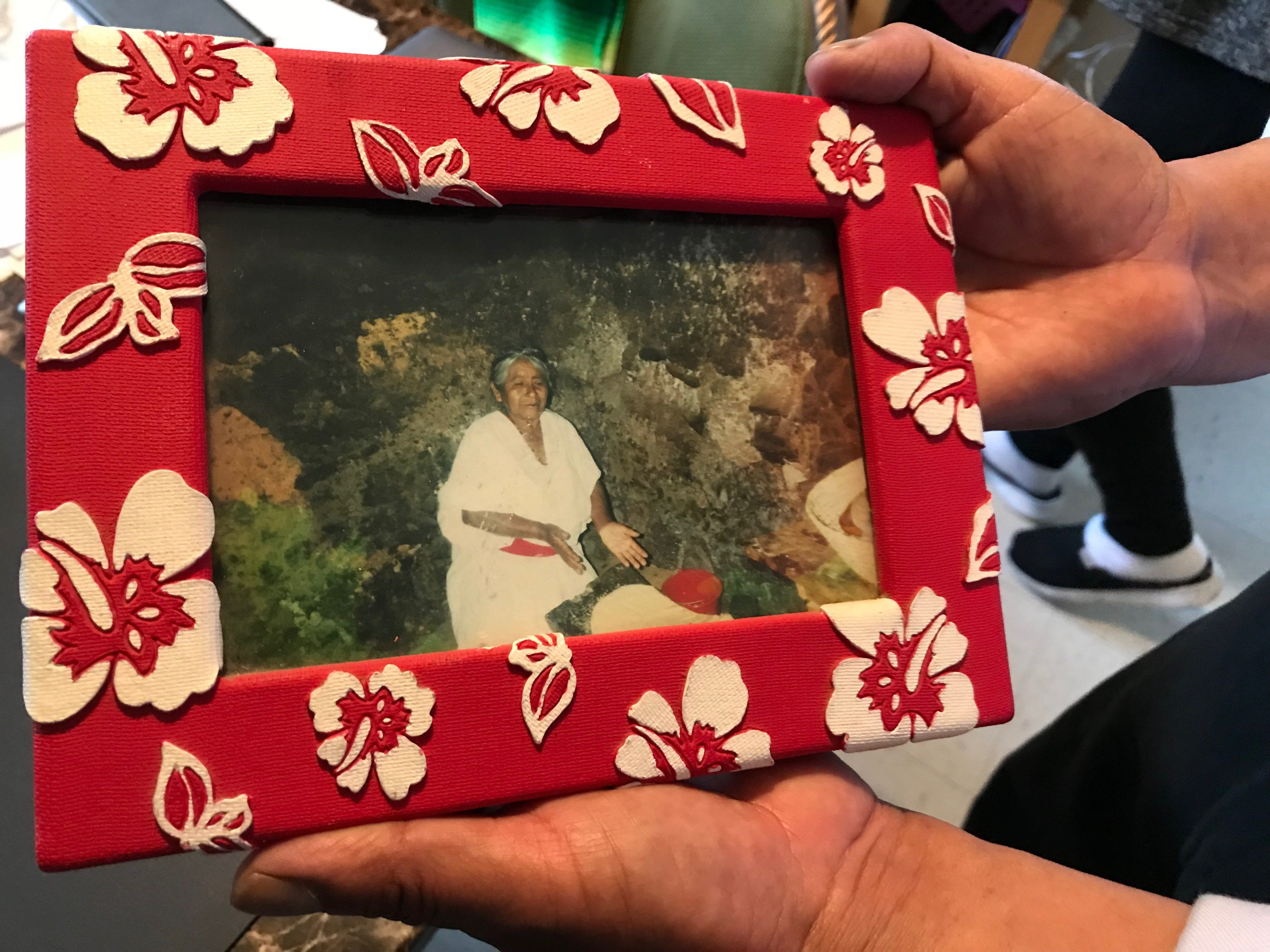 Adolfo González holds a picture of his 91-year-old mother Carmen, showing her making maza in their hometown in Oaxaca, México.