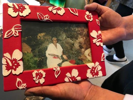 Adolfo González sostiene una foto de Carmen, su madre de 91 años, preparando masa en su pueblo natal en Oaxaca, México.
