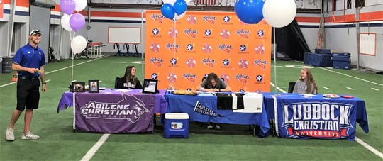 San Angelo Central High School girls soccer coach Ben Henry was all smiles as (from left to right) Addison Bonvaventure, Megan White and Madison Mayben made their college plans official Wednesday, May 15, 2019.
