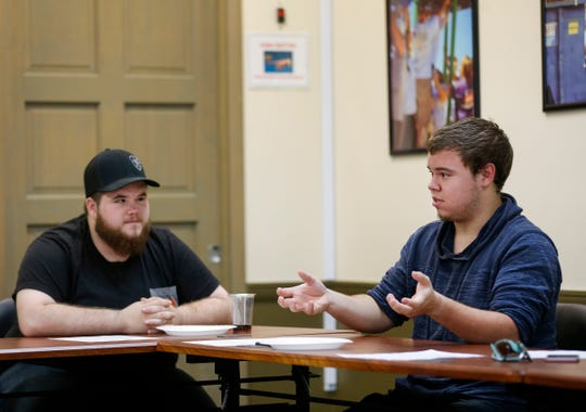 Tyson Walters, right, speaks as Garrett Foell, left, listens during a meeting of The Phoenix at the Community Partnership of the Ozarks on Tuesday, May 14, 2019.