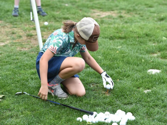 Chloe Widener, 8, puts a ball on the tee Wednesday afternoon at the Club of Ironwood as part of the First Tee golf instructional program.