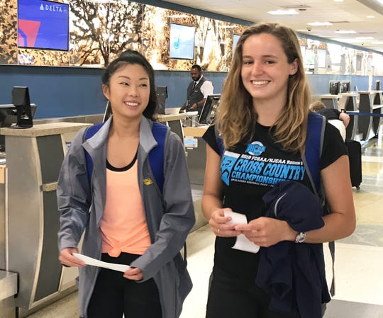 Mia Wiederkehr (left) and Genevieve Printiss receive their boarding passes for Hobbs, New Mexico. The will run at the NJCAA Outdoor Track & Field Championships.