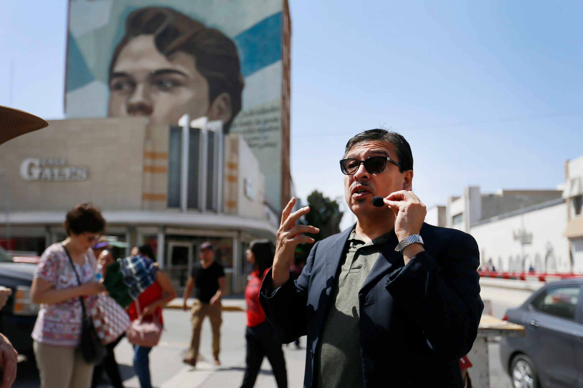 Thomas Cueva, UACJ professor of history, talks about the mural of Juan Gabriel during the Juárez historic walking tour lead by El Paso's first lady Adair Margo Thursday, May 16, in Juárez.