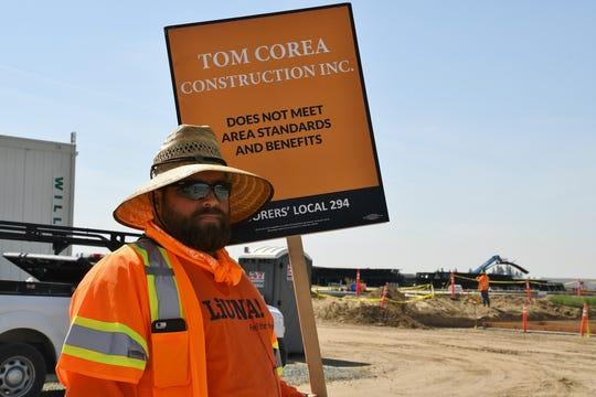Eddie Torres, a Laborers' International Union of North America member, pickets a Tom Corea Construction Inc. site near Riggin Avenue and Plaza Drive.