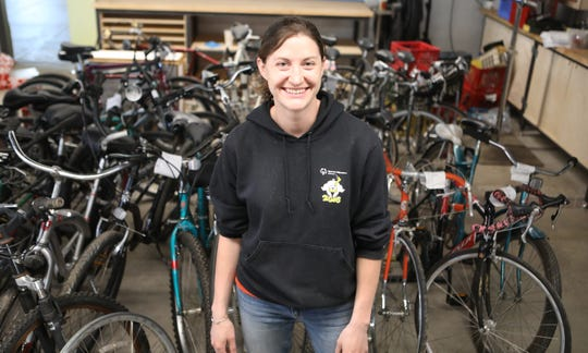 Laura Wilburn stands in front rows of bicycles.  Her organization, the Urban Bike Project of Wilmington, is celebrating a grand reopening of its location at 15th and Walnut Saturday.