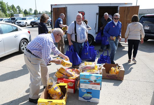 Several members of the Zanesville Noon Rotary organize bags of food as they prepared to dropped them off for 230 students at three elementary schools earlier this week.
