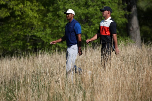 First round: Tiger Woods  and Brooks Koepka walk the course.