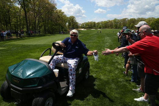 First round: John Daly high fives fans from his golf cart on the 12th hole.