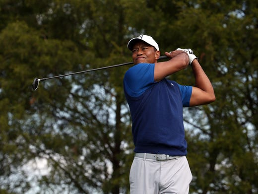 First round: Tiger Woods plays his shot from the 11th tee.