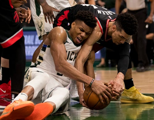 May 15: Bucks forward Giannis Antetokounmpo (34) hits the floor to try and corral a loose ball against Raptors guard Danny Green (14) during Game 1.