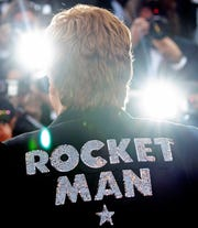 "Elton John poses for photographers upon his arrival at the premiere of the film ""Rocketman."""