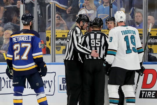 On-ice officials discuss whether they saw a hand pass, but none of them did.