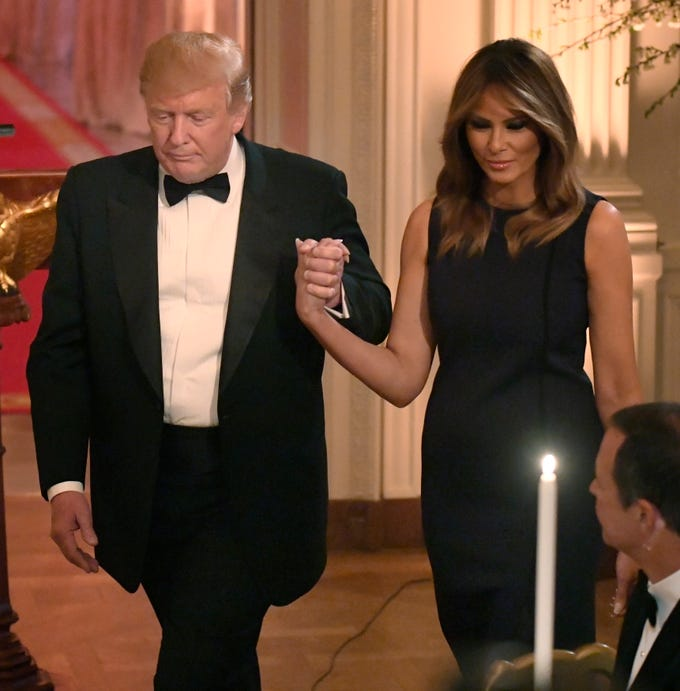 President Donald Trump holds hands with first lady Melania Trump after opening remarks during a White House Historical Association dinner at the White House, May 15, 2019.