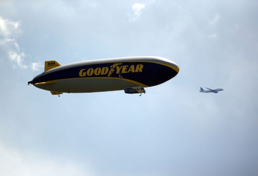 First round: A plane flies by the Goodyear blimp.