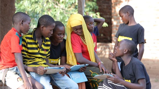 In this undated photo provided by XPRIZE, children in a village in the Tanga region of Tanzania gather to learn from tablets using open-sourced software that would easily be downloaded by illiterate children to teach themselves to read. That's what nearly 200 teams from around the world have spent more than a year in impoverished villages in Tanzania trying to do. The winner of this latest competition for a $10-million XPRIZE for global innovation is being announced Wednesday, May 15, 2019, in Los Angeles.