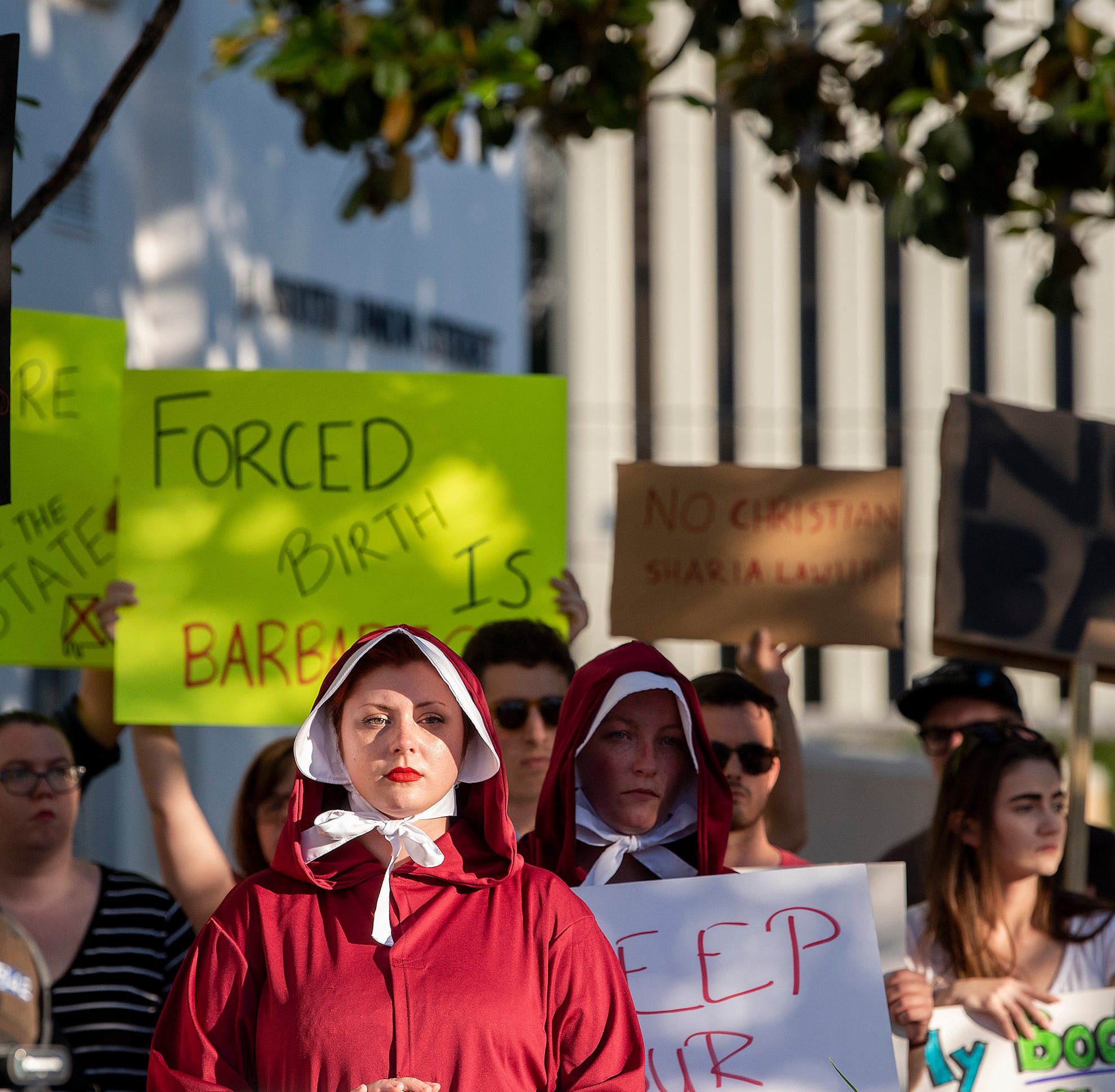 Margeaux Hartline, dressed as a handmaid, protests against a ban on nearly all abortions outside of the Alabama State House in Montgomery, Ala., on May 14, 2019.