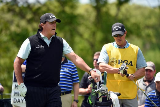 First round: Phil Mickelson with his caddie Tim Mickelson, right, on the second tee.