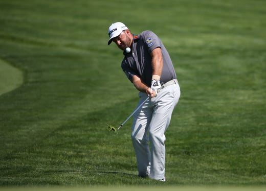 First round: Graeme McDowell chips onto the 11th green.