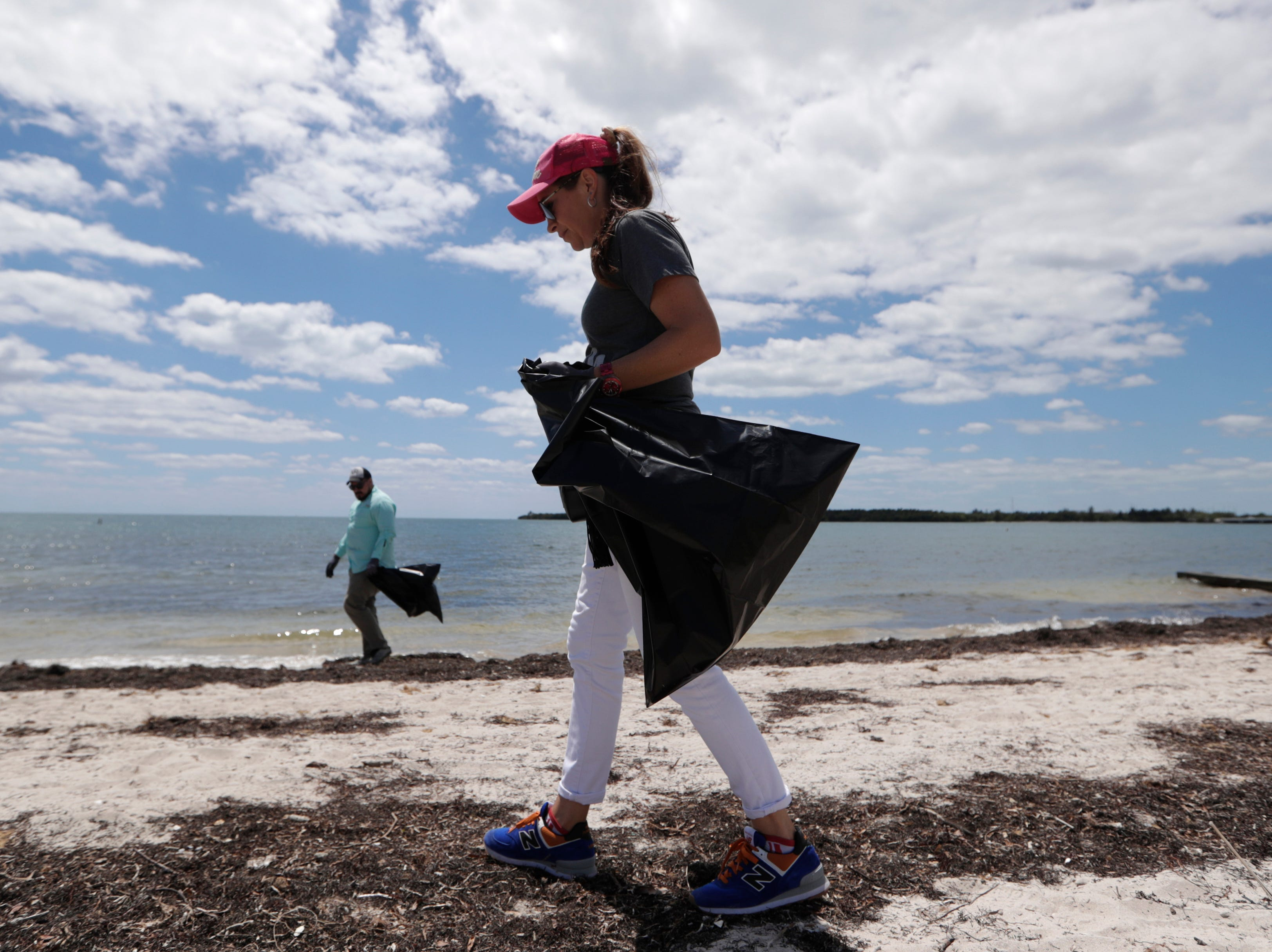 Volunteers pick up trash on Earth Day at Virginia Key Beach Park on April 22, 2019, in Miami.