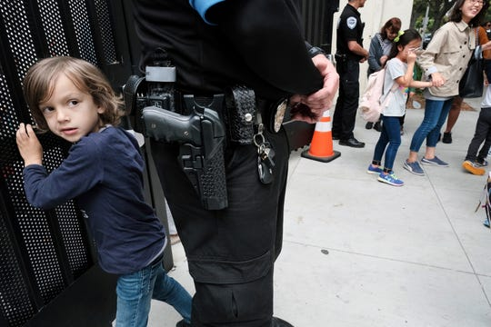 In this Monday May 13, 2019 photo Julian Richner, 9, leaves school for the day to meet his mother as he passes behind a security guard at Beverly Hills Unified School District's K-8 Horace Mann School in Beverly Hills, Calif.