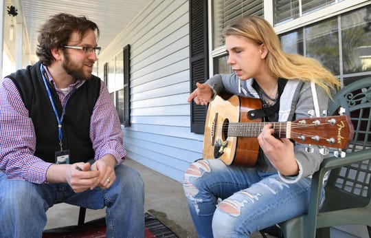 """Reporter Mike Ellis, left, listens to Kaylee Muthart of Anderson explain why she likes playing guitar in 2018, learning the chords to Green Day's """"Time of Your Life."""""""