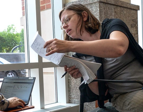 Nikie Mayo, right, checks her notes on assignment in 2019.