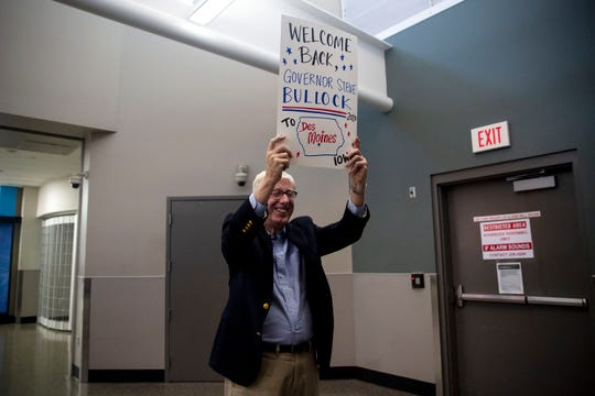 Iowa Attorney General Tom Miller holds a sign welcoming Steve Bullock, Governor of Montana, to Iowa as he arrives for his first campaign trip to the state on Thursday, May 16, 2019, at the Des Moines International Airport.